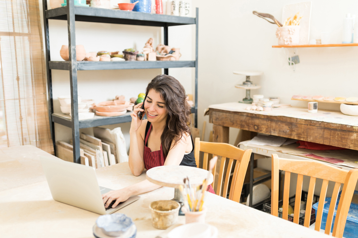 Artist Taking Online Pottery Orders Using Laptop And Smartphone