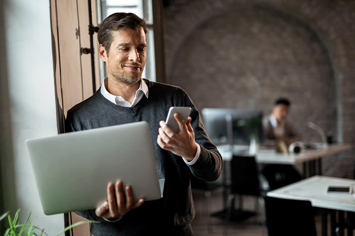 man looking at phone smiling whilst holding laptop in his hand