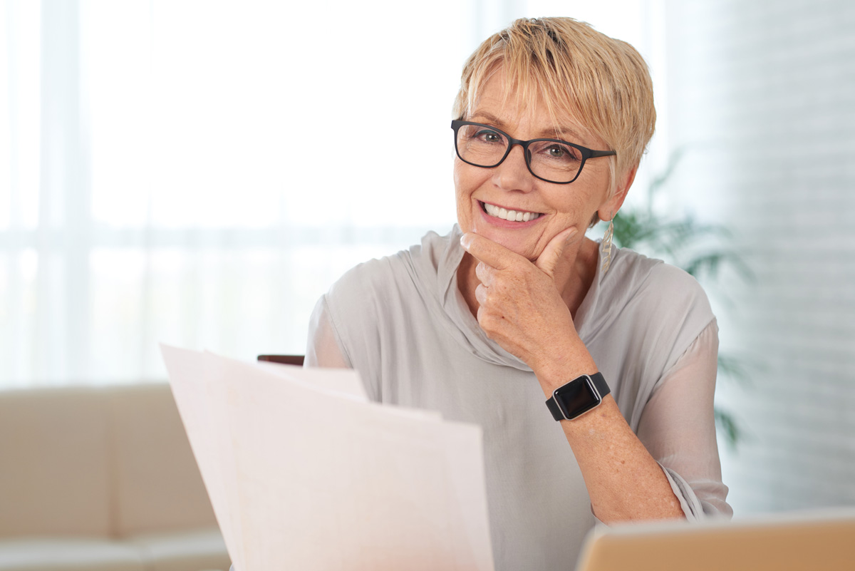 Portrait of smiling senior woman with documents looking at camera