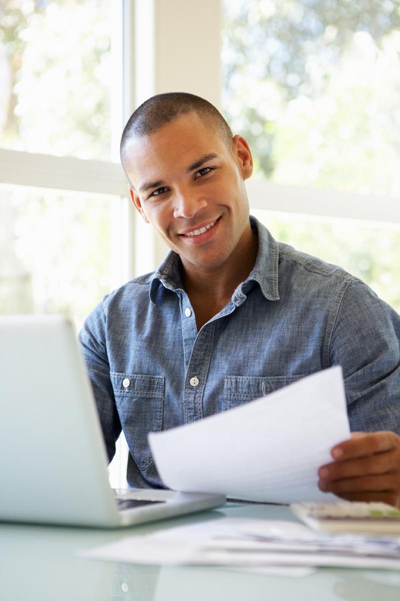 Young Man Using Laptop At Home Smiling At Camera