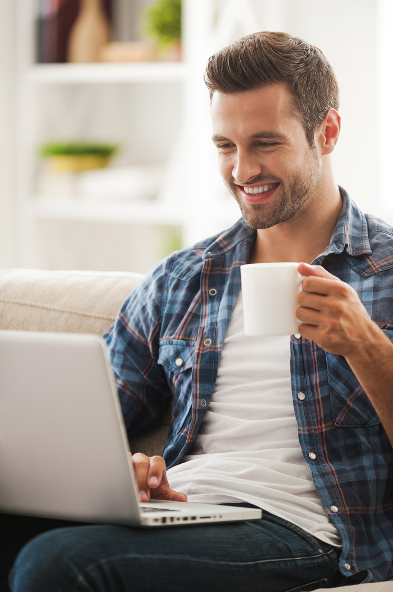 Smiling young man working on laptop and holding cup of coffee while sitting on sofa