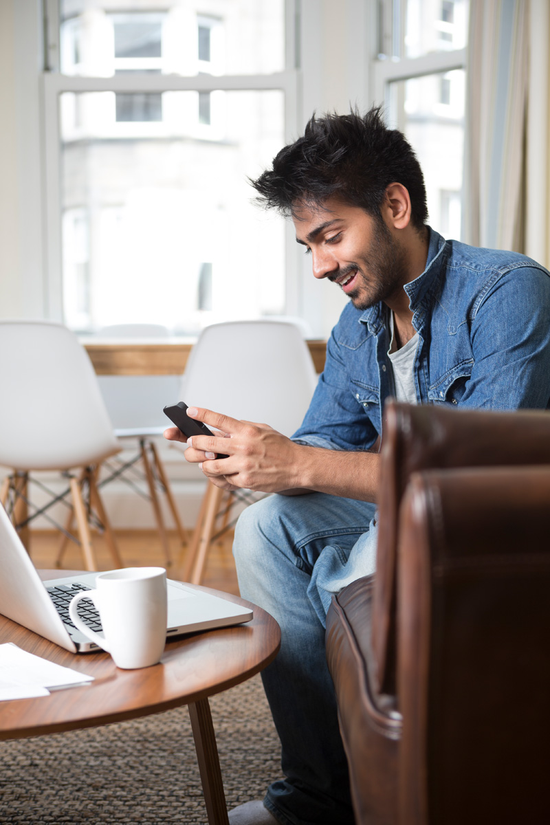 man using a mobile phone and working on his laptop