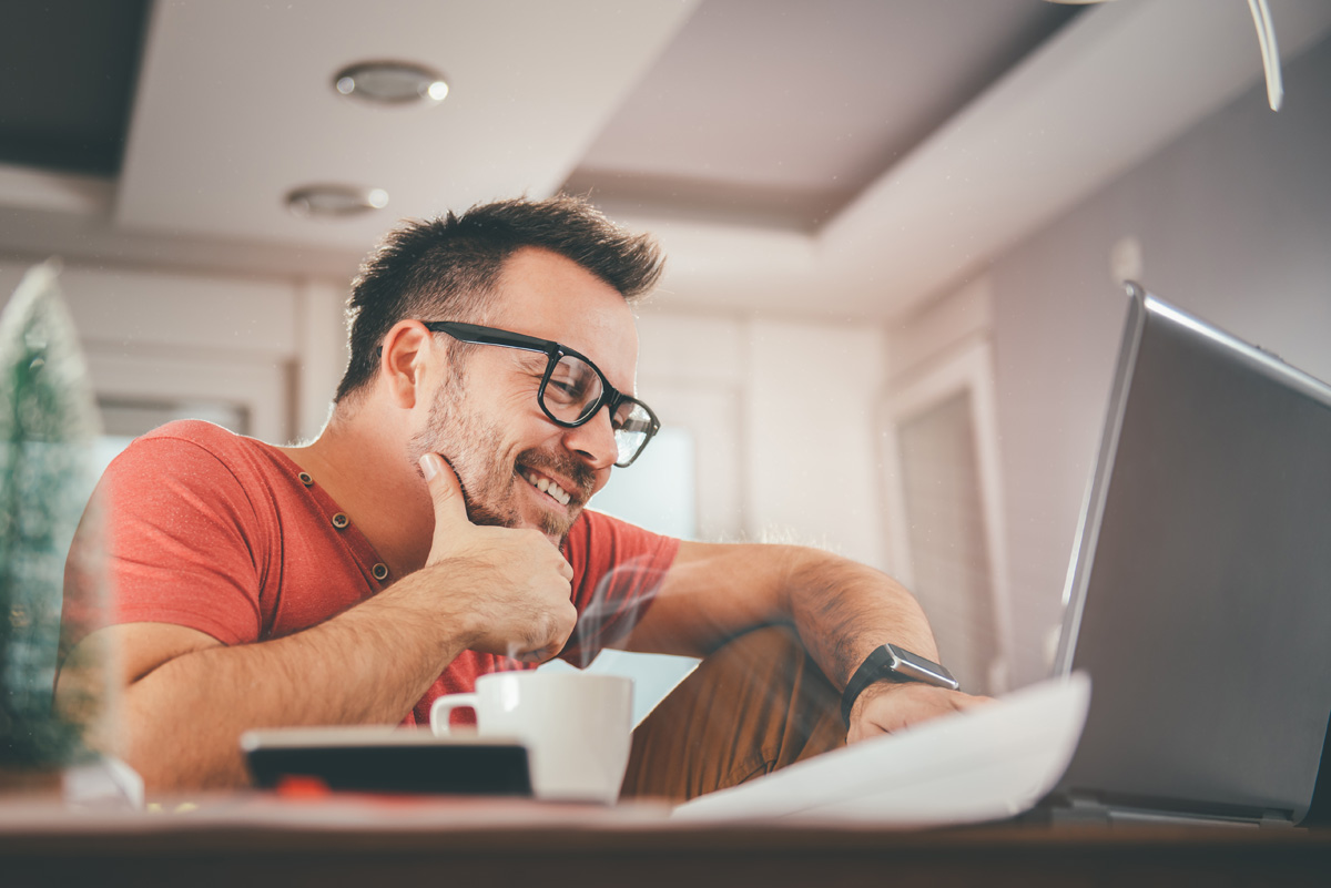 Man in red shirt smiling and using laptop at office