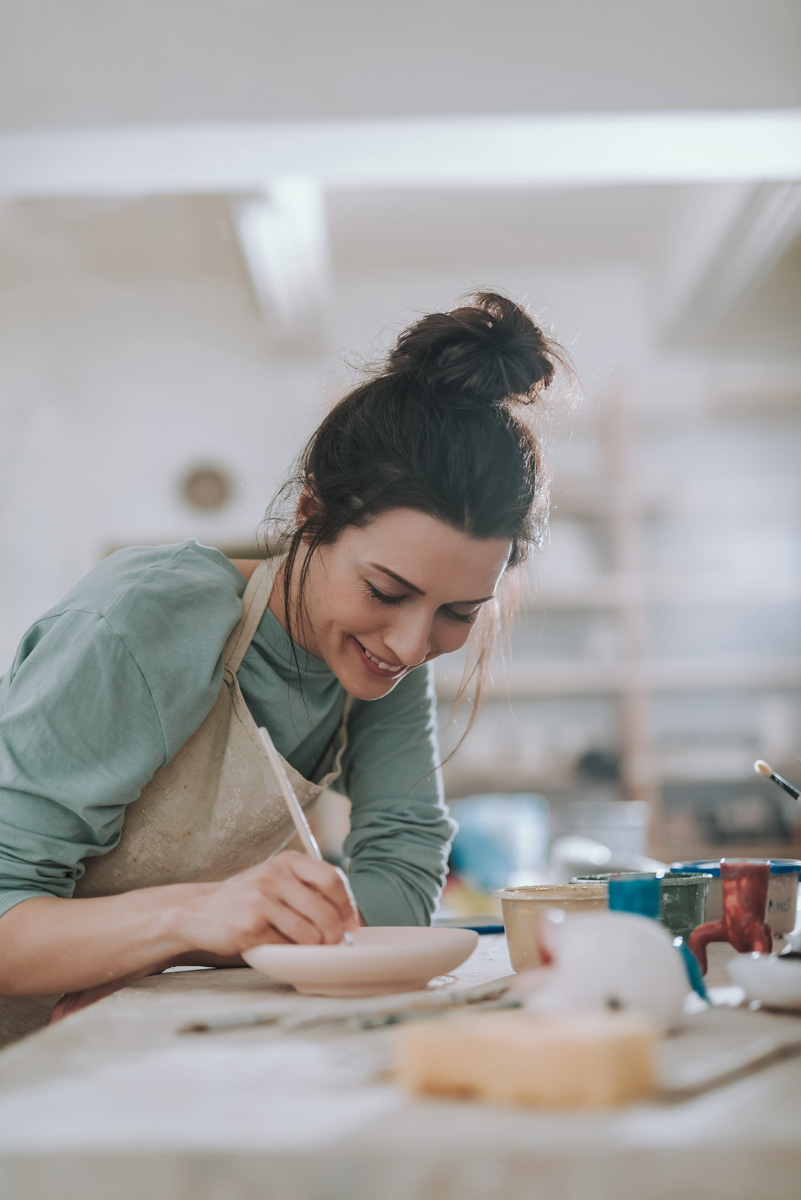 lady with hair tied up working on pottery