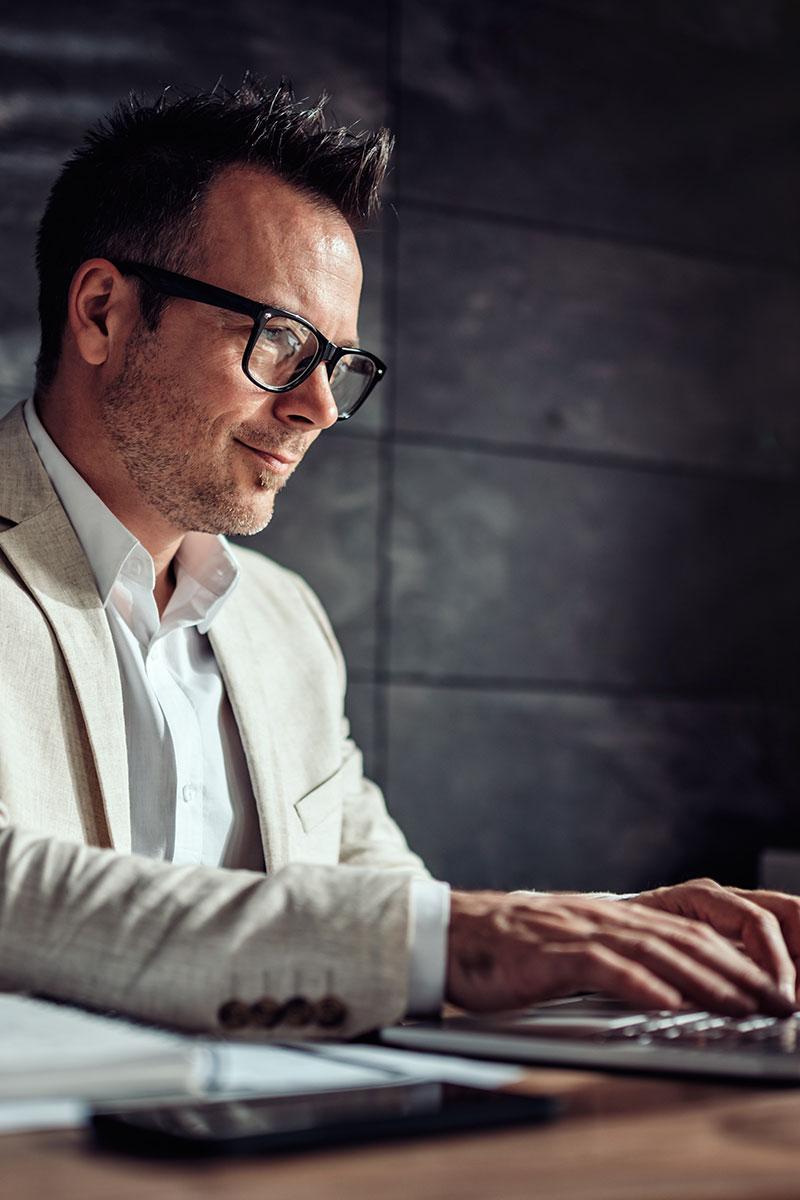 man wearing glasses typing on a keyboard