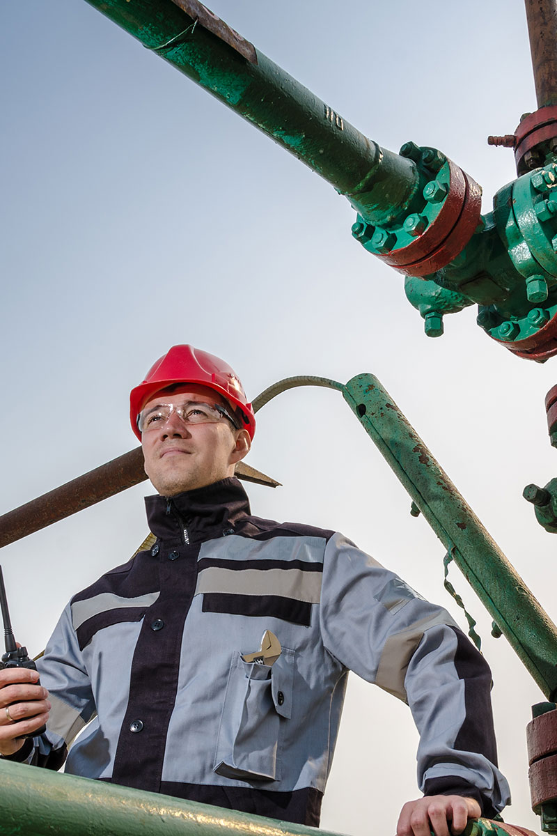 man wearing red hard hat working with gas pipes