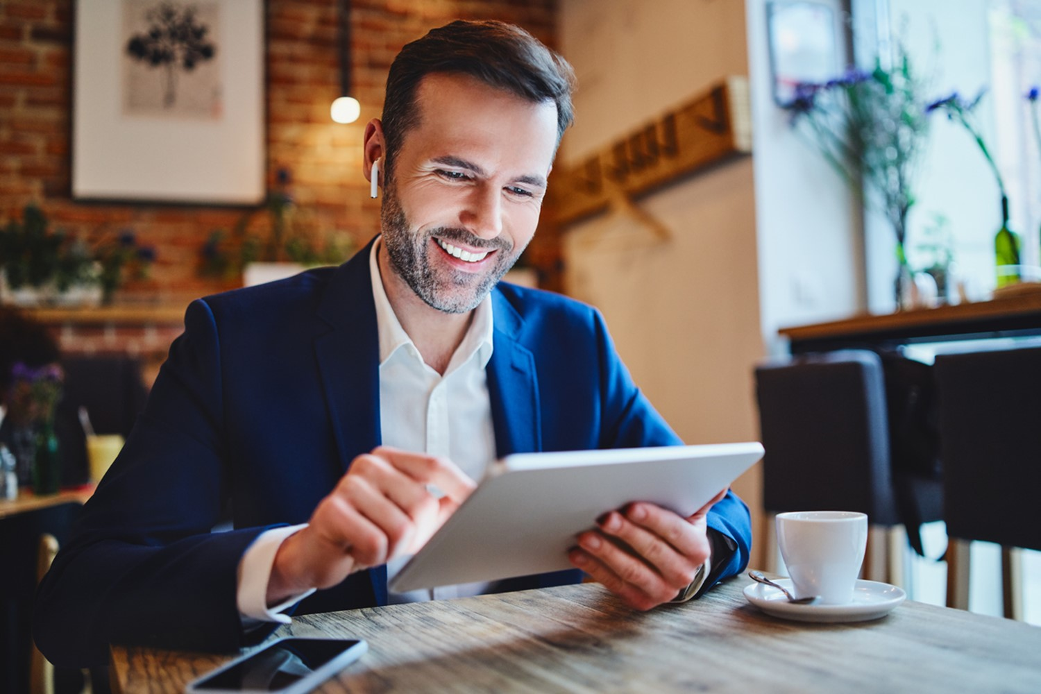 man on ipad/tablet smiling with an air pod in one ear looks like his in a coffee shop