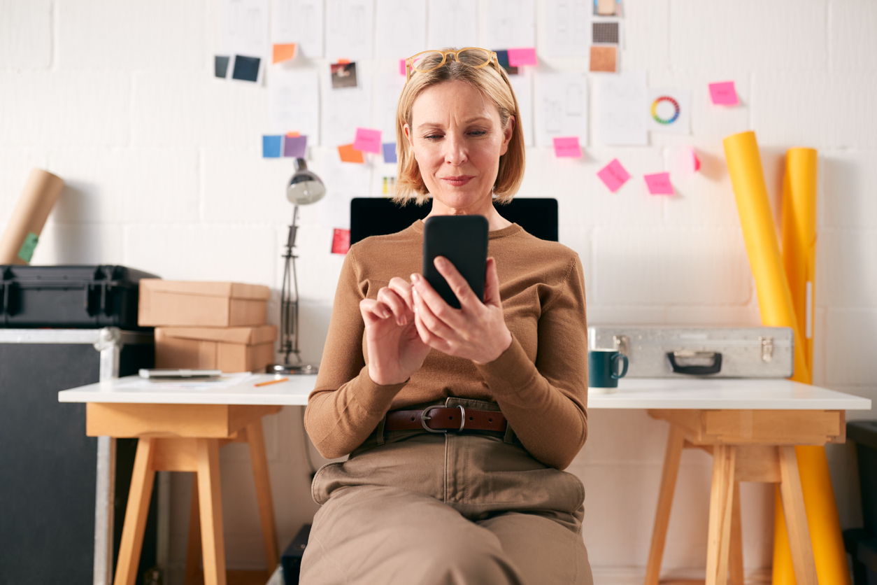 Businesswoman With Mobile Phone Working At Desk In Start Up Creative Business