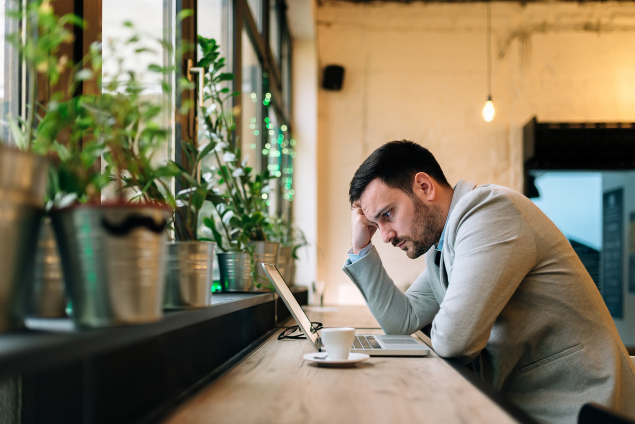 Worried man looking at laptop screen while sitting at modern cafe.