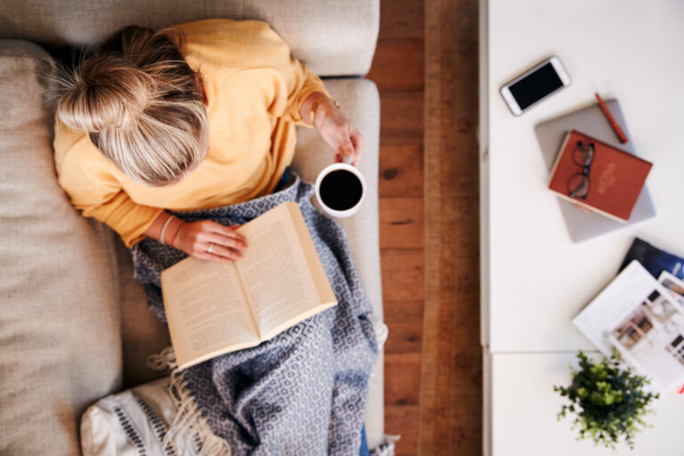 Overhead Shot Looking Down On Woman At Home Lying On chair Reading Book And Drinking Coffee