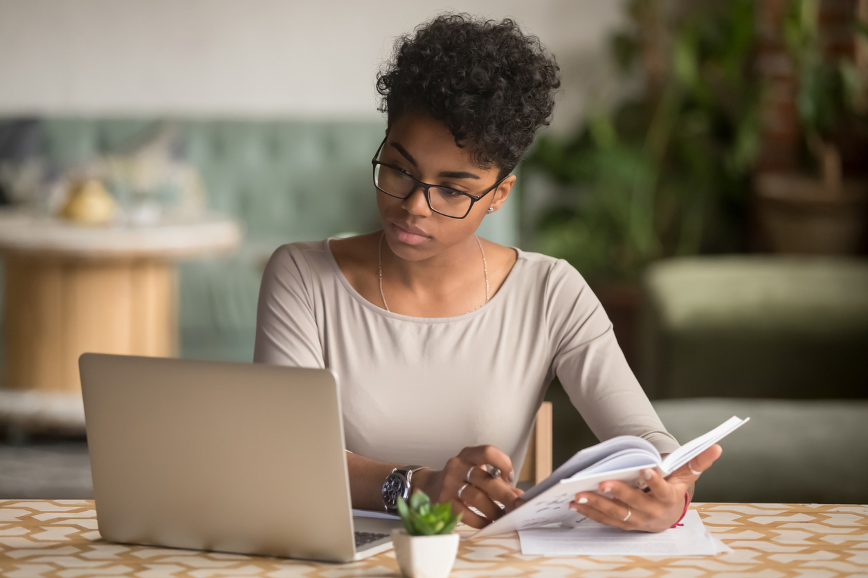 businesswoman or student looking at laptop holding book learning, serious black woman working or studying with computer doing research or preparing for exam online