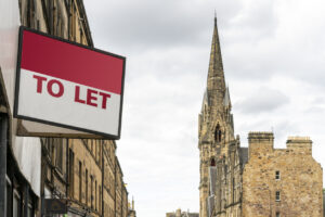 Estate agency 'To Let' sign board with typical British buildings in the background
