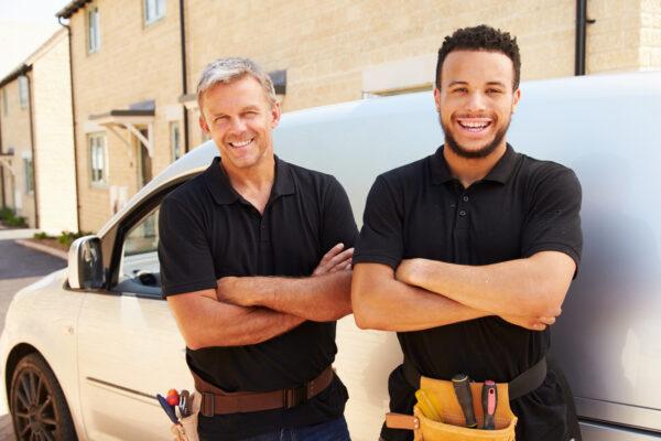 workmen-standing-in-front-of-van-smiling