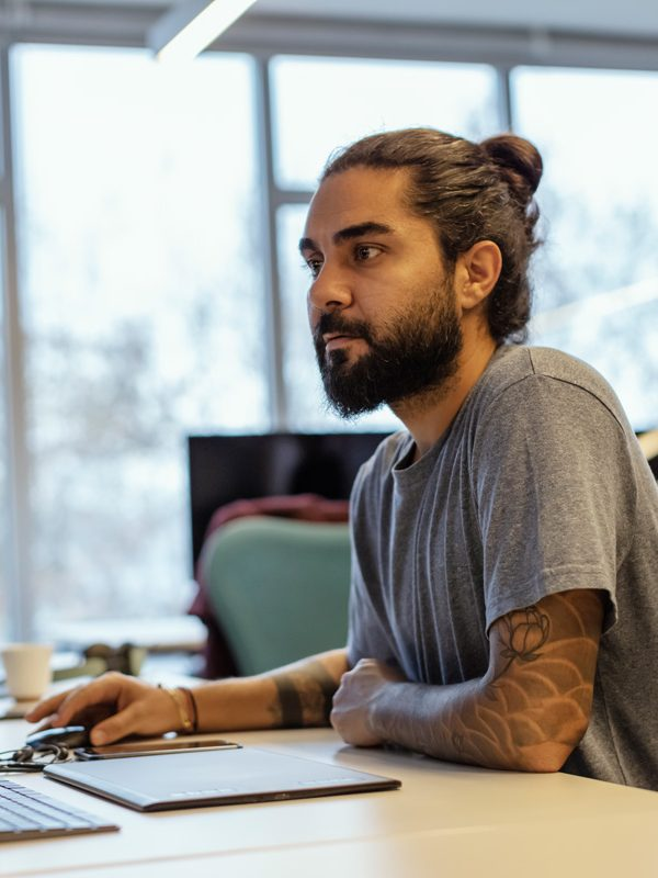 Portrait of man with Tattoo on arm working in office