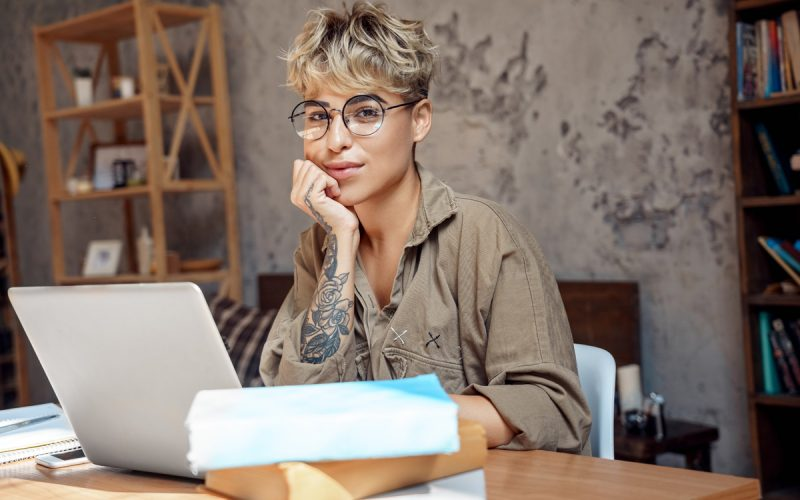 Young woman short hair wearing eyeglasses sitting at desk at library studying online on laptop distance education leaning on hand looking camera smiling playful