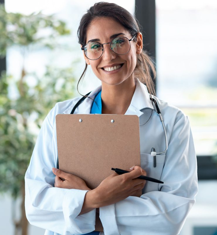 Shot of female doctor looking at camera and smiling while holding medical documents